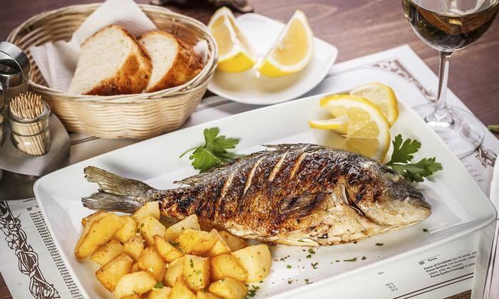 ארוחת דגים זוגית ממש מול הים עם שולחן עמוס בסלטים ודגים טריי...